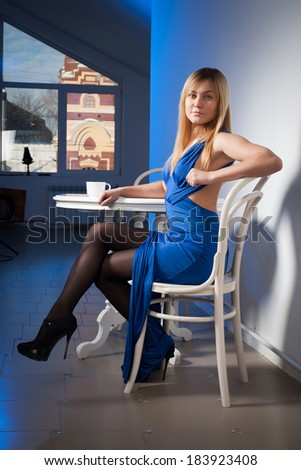 Girl in evening dress sits at table