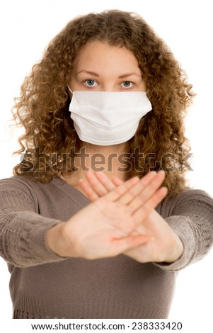 Girl in face mask stretch out palms in warning gesture with girl in focus