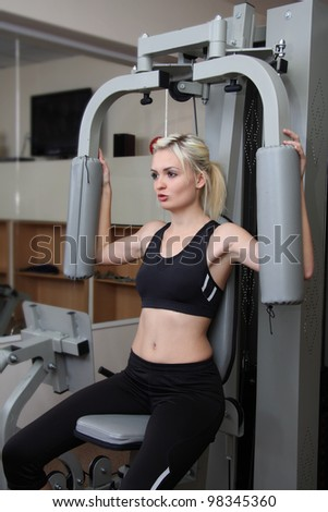 girl in fitness club. Against sports training apparatus. - stock photo