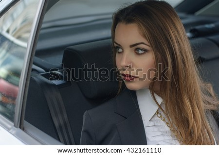 Girl in formal clothes rides in a car sitting in the back seat of the car. Concept: transport, lifestyle, fashion