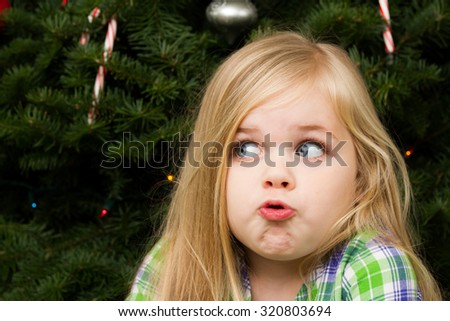 Girl in front of the christmas tree making a funny face - stock photo