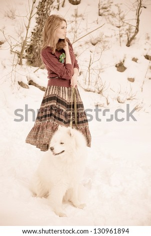 Girl in fur hat with samoyed dog in winter park - stock photo