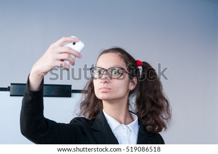 Girl in glasses with pigtails makes selfie