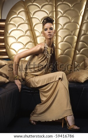 girl in gold dress sitting on chair - stock photo