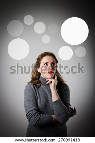 Girl in grey having an idea with grey bubbles over her head. - stock photo