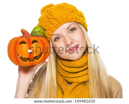 Girl in hat and scarf showing jack-o-lantern - stock photo