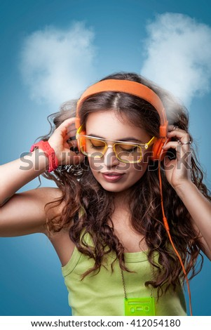 Girl in headphones with closed eyes listening to music, enjoying music, blowing white smoke coming out of ears.Closeup portrait girl on blue background.Positive human emotion facial expression feeling - stock photo