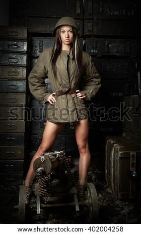 Girl in helmet and gun - stock photo