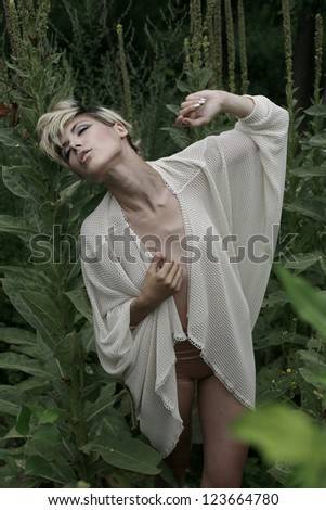 girl in her underwear on the lawn looking up - stock photo