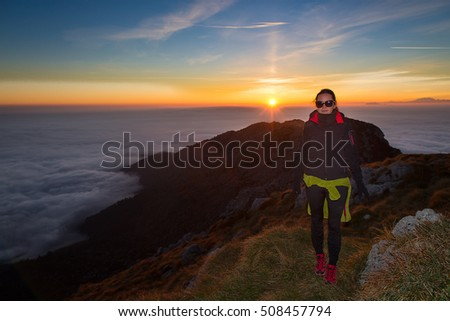 Girl in high mountains sunset in the mountains with a sea of clouds in the valley