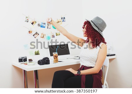 Girl in home office taking a selfie on action camera. Modern beautiful curly redhead young freelance photographer woman in contemporary photography studio home office. No retouch, mild matte filter.
