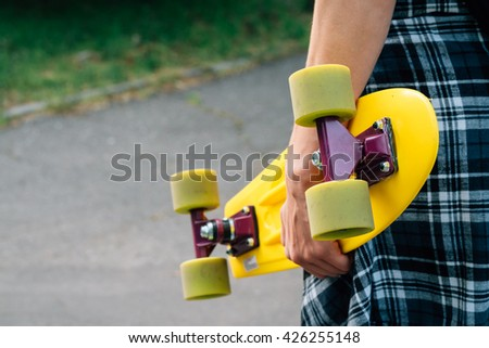 Girl in jeans and a plaid shirt holding a yellow plastic skateboard with green wheels. View from the back. - stock photo