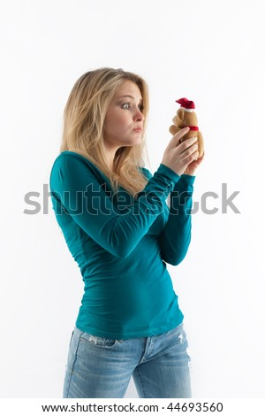 Girl in jeans and top staring at a teddy bear isolated on white.