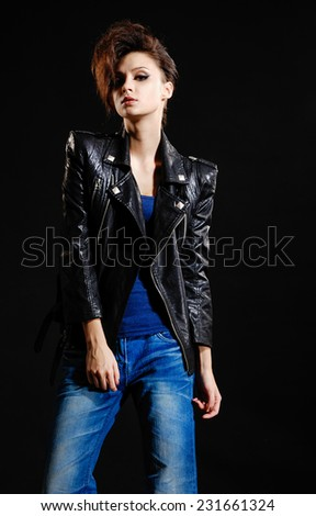 girl in jeans, posing standing on black background - stock photo