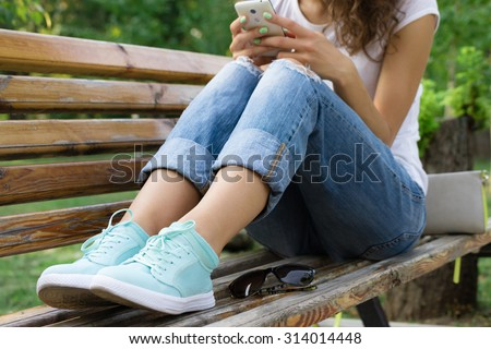 Girl in jeans sits on a park bench and using a mobile phone - stock photo