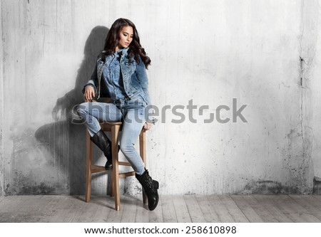 Girl in jeans sitting on wooden chair - stock photo