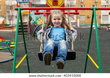 Girl in jeans suit swinging in a playground