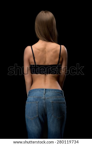 Girl in jeans with naked back relief. Isolate on black. - stock photo