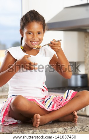 Girl In Kitchen Eating Bowl Of Breakfast Cereal
