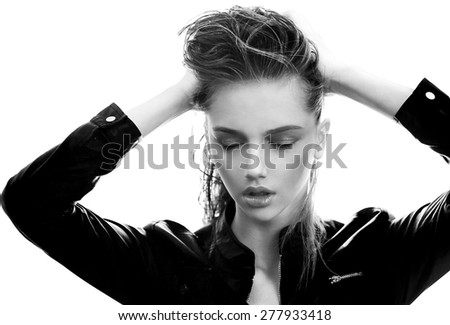 girl in  leather jacket does up hair hands - stock photo