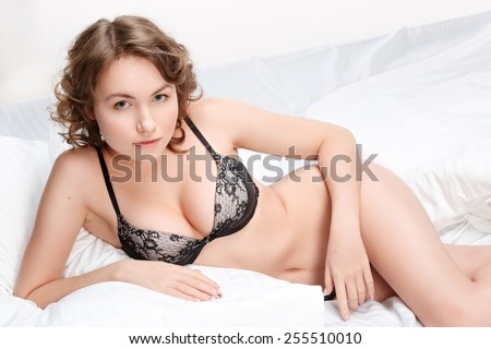 Girl in lingerie on the bed. Sexy brunette on white bed sheets. The morning sun in the bedroom. - stock photo