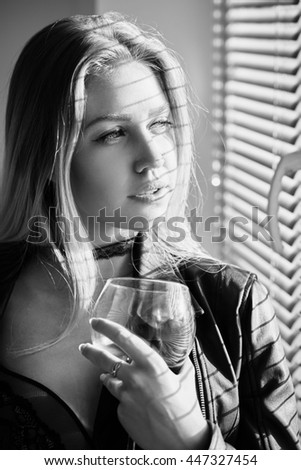 girl in lingerie with wineglass looking at window, monochrome image - stock photo