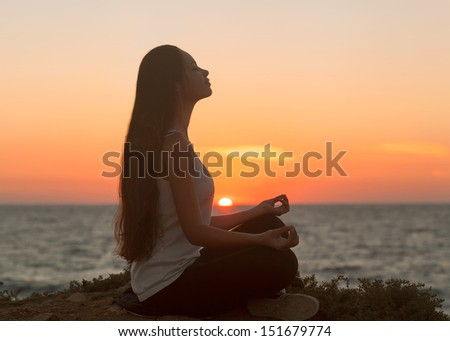 Girl in lotus pose at sunset.Asian Caucasian female model.  - stock photo