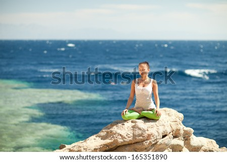 girl in lotus position on the rock by the sea - stock photo