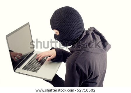 Girl in mask stealing data from laptop - stock photo