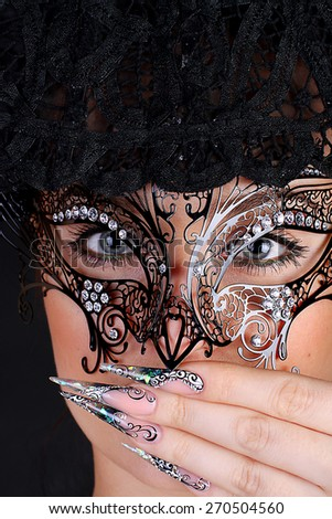 Girl in mask with acrylic manicured beautiful nails - stock photo