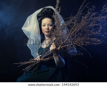 girl in medieval dress  with bunch of sticks in smoke