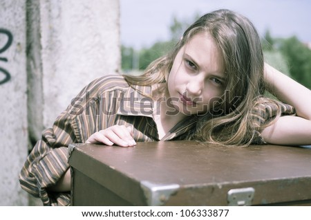 Girl in men's shirt near suitcase in unreconstructed building