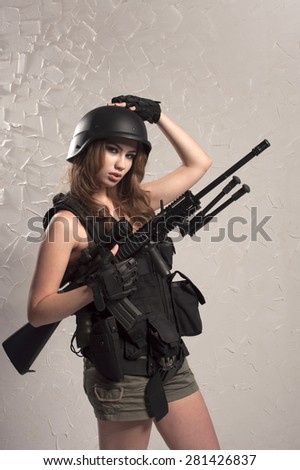 Girl in military outfit with gun on gray background