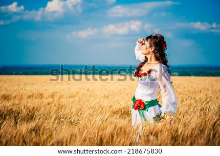 girl in national ukrainian clothes on the wheat field. Bride in the national Ukrainian costume laughing in a wheat field in a sunny summer day - stock photo