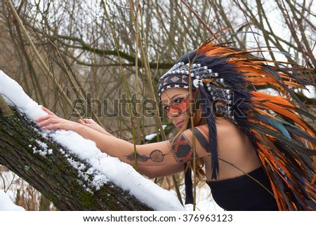 Girl in native american headdress climbs tree