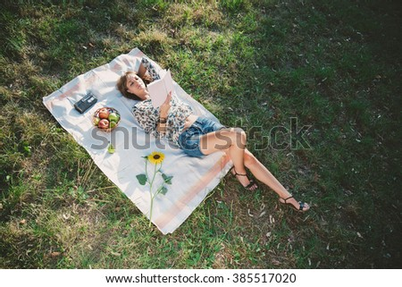 Girl in nature lying on the grass and reading book - stock photo