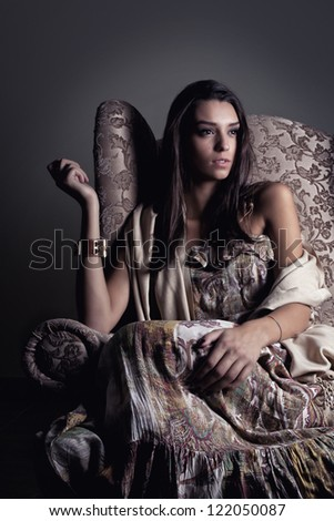 Girl in old armchair thinking