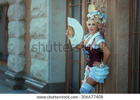 Girl in old clothes and vintage hair on his head. The fan in her hand. - stock photo