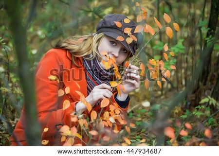Girl in orange coat looking through autumn leaves.