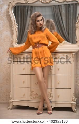 girl in orange dress, near the dresser - stock photo