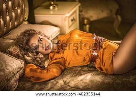 girl in orange dress on the bed - stock photo