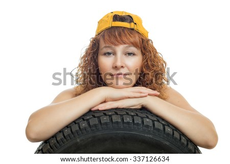 Girl in overalls and a baseball cap keeps car tire
