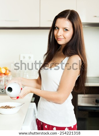 Girl in pajamas having breakfast in the kitchen