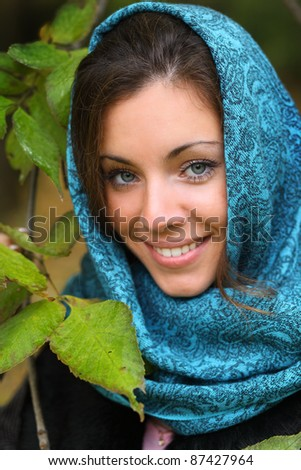 Girl in park colourful autumn. Beautiful lady in headscraft and vivid foliage - stock photo