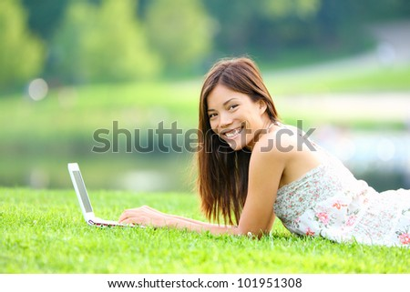 Girl in park on laptop. College student studying on laptop in summer or spring city park. Beautiful happy mixed race Caucasian / Asian chinese university student lying in the grass outside. - stock photo