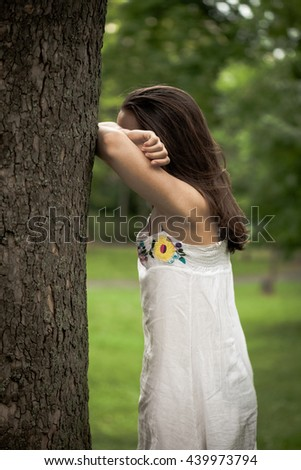 girl in park play hide and seek summer day
