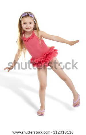 Girl in pink bathing suit with tutu poses, standing on one leg - stock photo