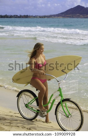 girl in pink bikini on her bike at the beach with surfboard - stock photo