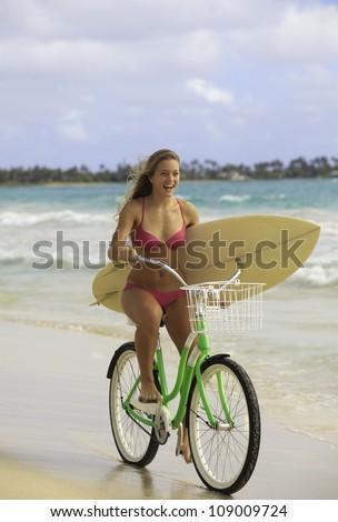 girl in pink bikini riding her bike on the beach with surfboard - stock photo