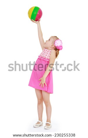 Girl in pink dress holding a ball.Very cheerful little girl. - stock photo